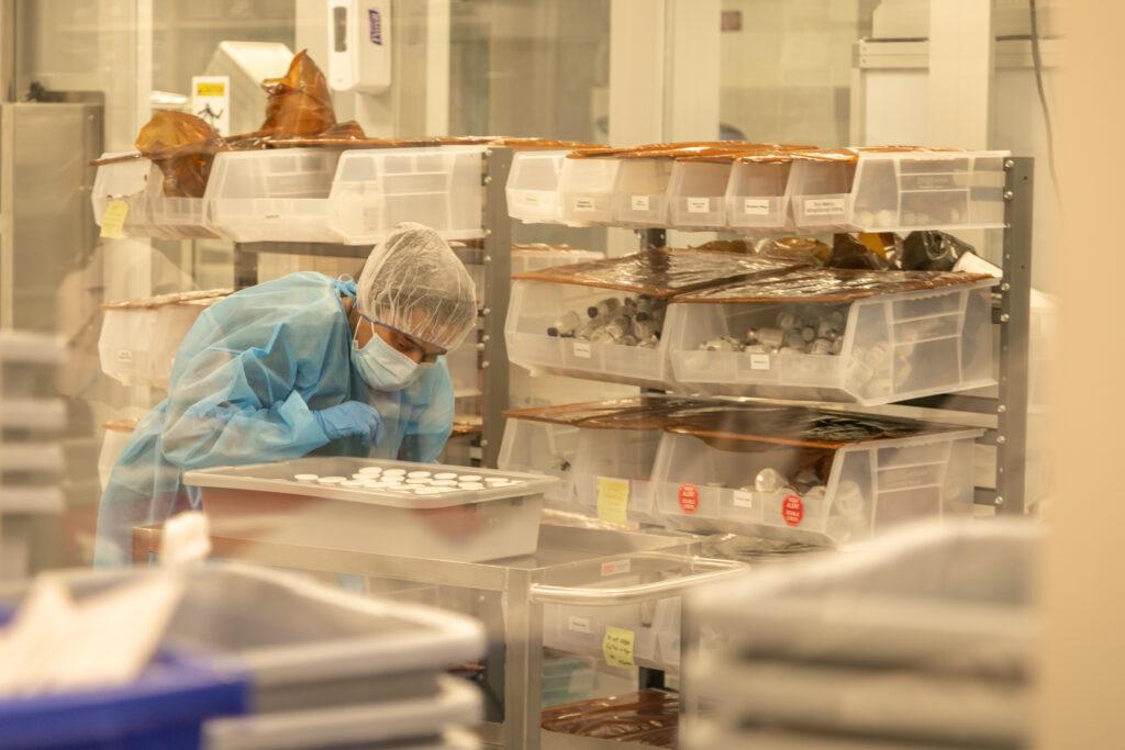 Employee in Yurek Specialities clean room looking at a cart with medicine