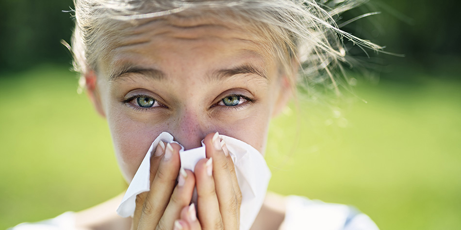 Teenage girl with allergy blowing nose