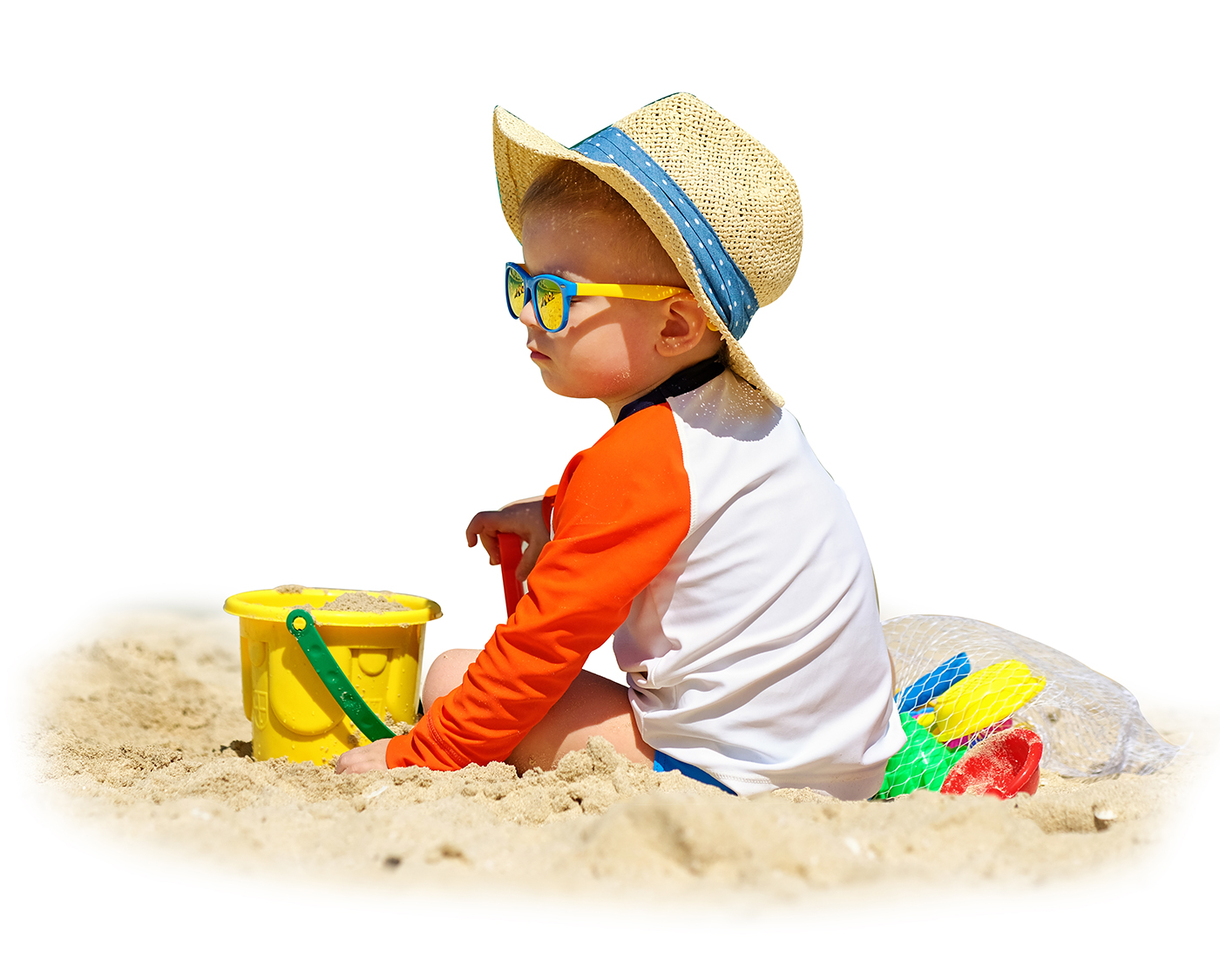 Two-year-old toddler boy playing with beach toys on beach
