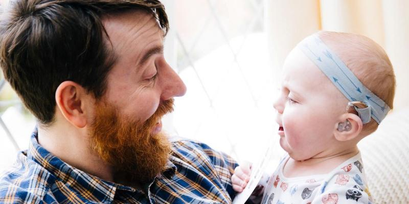man holding infant with hearing aid