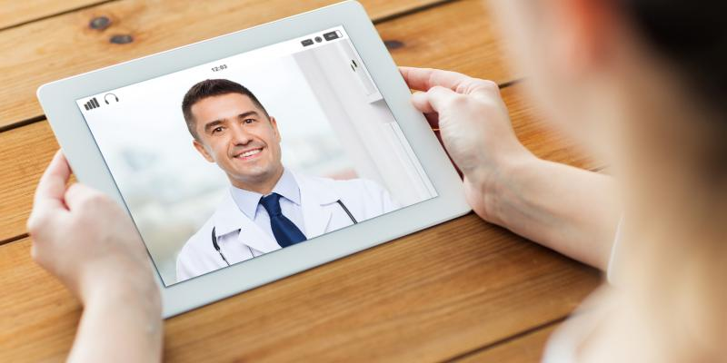 Women holding electronic device, on a virtual call with doctor.