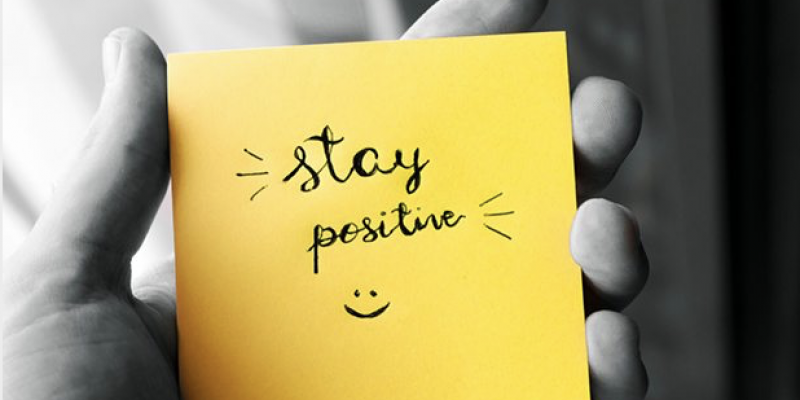 Hand holding yellow post it note saying stay positive