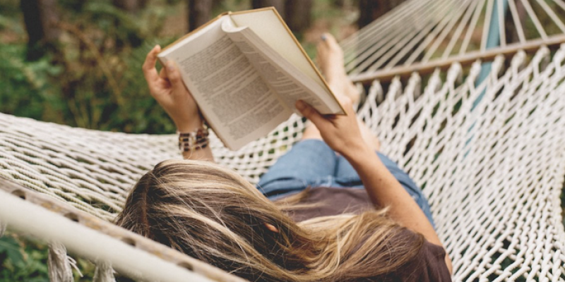 A person reading a book on a hammock
