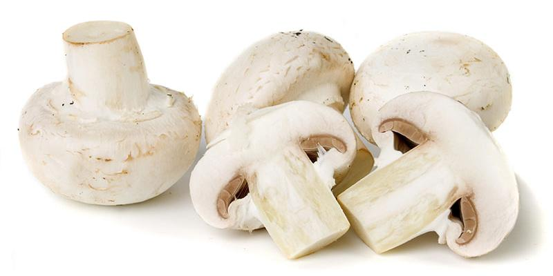 Three white button mushrooms with one sliced in half.
