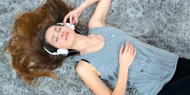 a person laying down with head phones listening to music
