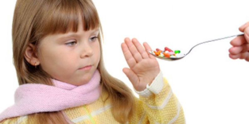Child putting her hand in front to stop from a spoonful of pills
